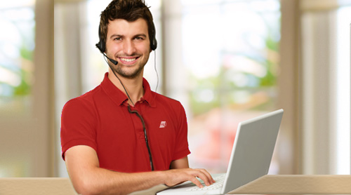 man wearing red clothes calling with headphones and a computer