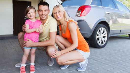 Family posing by their car in the driveway.