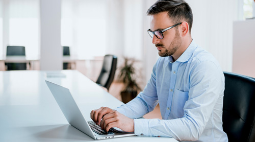 Man with glasses using a laptop
