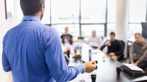 Man doing a speech to his colleagues during a meeting in an office